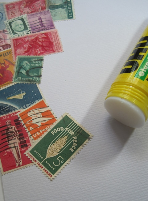 Vintage stamps to cover background using glue stick Lefko