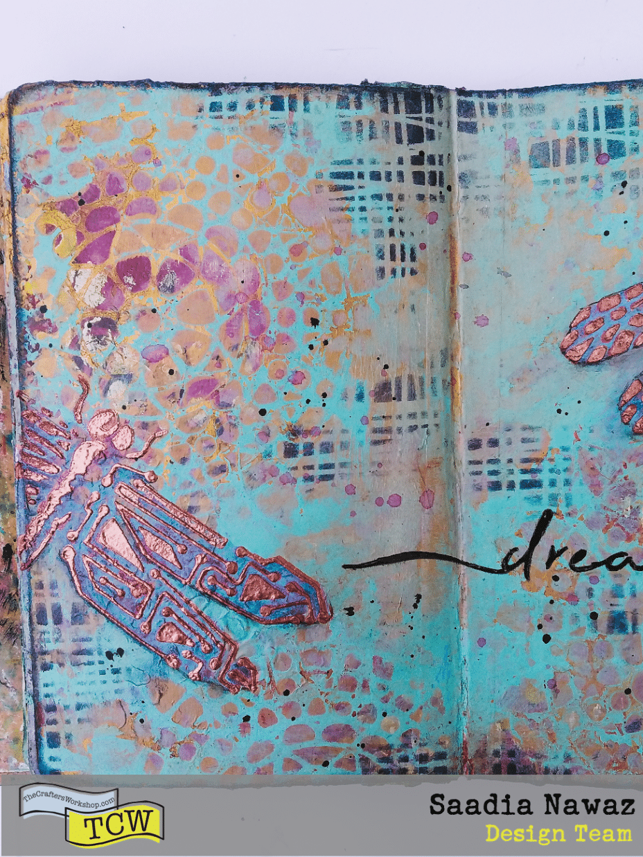 A journal spread with copper penny modeling paste, stencils, gesso