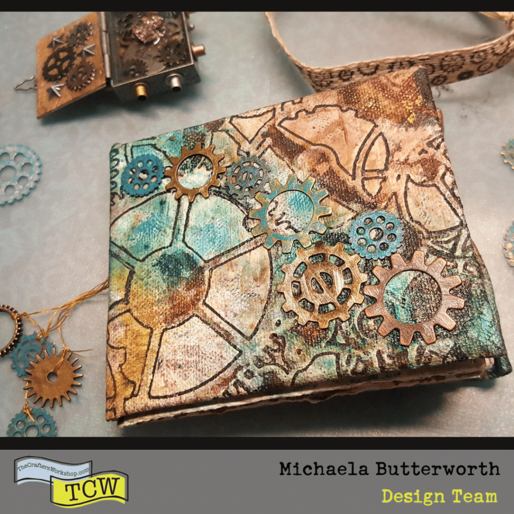 Image of Steampunk Junk mini journal front cover laying on table surrounded by steampunk gears and props.