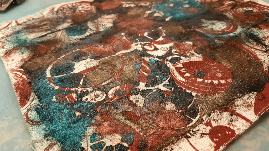 Image showing the cover fabric which has now been stamped, stencilied with black gesso, and sprayed with color spray.