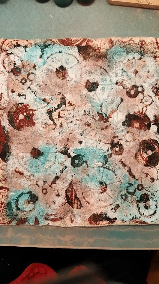 Image showing a birds eye view from above, looking down at the white gesso, now dried, over the color sprays on the fabric.