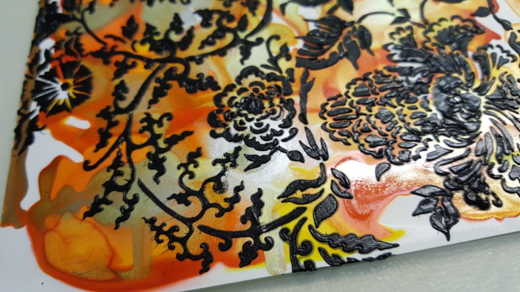 Black modeling paste applied with a palette knife through the Asian Floral stencil on top of yellow, gold, orange, and red alcohol inks on medium weight yupo paper.