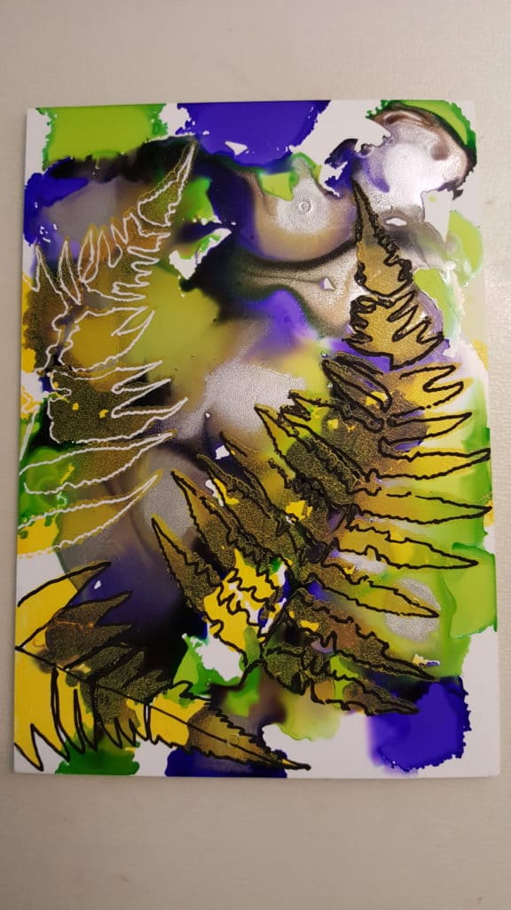 Yupo paper with purple, green, and yellow alcohol inks beneath stenciled fern fronds with black and white Signo uni-ball pens.