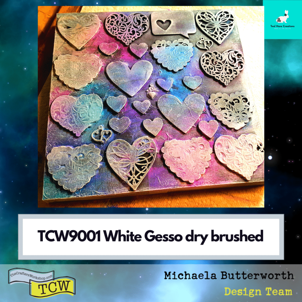 The wood panel embellished with hearts and tissue paper is sprayed with colorful mica inks, then dry brushed with white gesso to make the details stand out.
